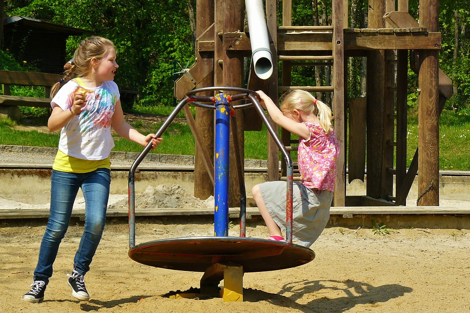 2 children playing on a merry go round